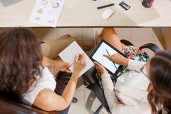 Teamwork Två unga affärskvinnor diskuterar affärsplan royaltyfri fotografi
