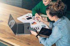Teamwork Två unga affärskvinnor som framme sitter på tabellen av bärbara datorn På tabellen är minnestavladator- och pappersdiagr Arkivfoton