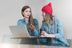 Teamwork två unga affärskvinnor som sitter på tabellen i kafé och att dricka kaffe och samtal fotografering för bildbyråer