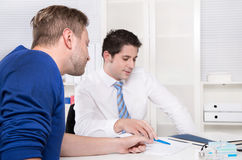 Teamwork: two business men sitting at desk at office. Royalty Free Stock Image
