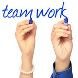 Teamwork. Two hands writing the word teamwork Royalty Free Stock Image