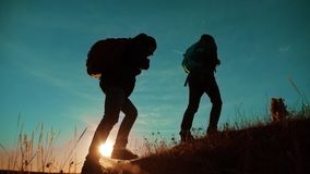 Free Teamwork. Two Hikers Enjoying Sunrise Walking From Top Of A Mountain And Dog. Slow Motion Video. Two Hikers With Royalty Free Stock Photography - 139668267