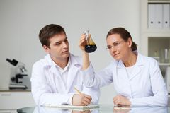 Teamwork. Two scientists looking at glass flask with liquid oil in laboratory Stock Photography