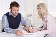 Teamwork between two work colleagues at desk at office. Royalty Free Stock Photography