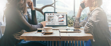 Teamwork, two young businesswomen sitting across table from each other. On table laptop, coffee cup and tablet computer. First girl showing pencil on computer Stock Images