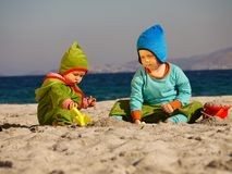 Teamwork. Two young children playing together in the sand Royalty Free Stock Photos