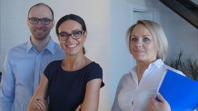 Teamwork von jungen Leuten im Büro, das zur Kamera und zum Lächeln schaut Stockbilder