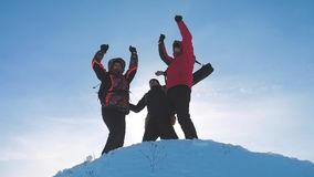 Teamwork winners. group team tourist hikers success win winter reached the top of the mountain silhouette sunlight