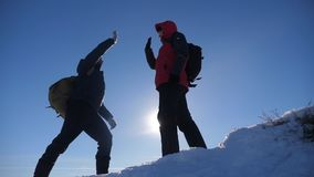 Teamwork winners tourists winter snow business travel trip met on top of a mountain. Two men with backpacks hiking met. In the silhouette in mountains with stock footage