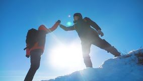 Teamwork winners tourists winter snow business travel trip met on top of a mountain. two men with backpacks hiking met
