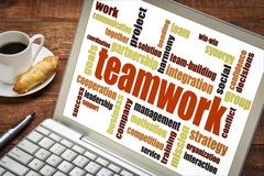 Teamwork word cloud on a laptop. With a cup of coffee royalty free stock image