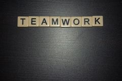 Teamwork word tiles lined up on a black background. Concept. Working together. Business, education, life. royalty free stock photos