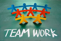 Teamwork words and colorful paper dolls Stock Photos