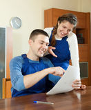 Teamwork of workers in uniform looking financial documents at ta Stock Photo
