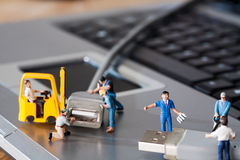 Teamwork In The Workplace. A team of miniature toy model artisans repairs data cables Royalty Free Stock Photo