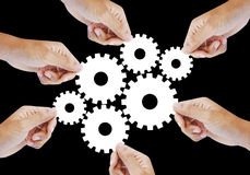 Teamwork works together to build a cog wheel gear system. Royalty Free Stock Photos