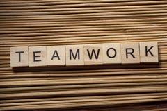 TEAMWORK-Wort geschrieben auf Holz-ABC-Block am hölzernen Hintergrund Stockbild