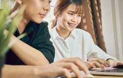 Teamwork, Young businesswoman in office in casual shirt. Selecting information with colleagues with a computer on the table. Royalty Free Stock Photography