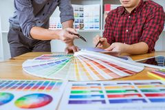 Teamwork of young creative designers working on project together and choose color swatch samples for selection coloring on digital royalty free stock images