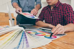 Teamwork of young creative designers working on project together and choose color swatch samples for selection coloring on digital royalty free stock photo