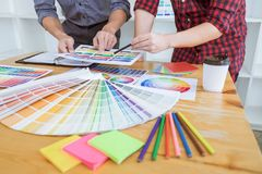 Teamwork of young creative designers working on project together and choose color swatch samples for selection coloring on digital. Graphic tablet at workspace royalty free stock photos