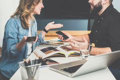 Teamwork, young designers are sitting at table in office and pick up finishing materials in catalog. Business meeting. royalty free stock image