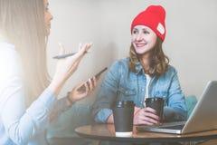 Teamwork, zwei junge Geschäftsfrauen, die bei Tisch im Café, in trinkendem Kaffee sitzen und online arbeiten stockfotos