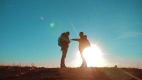 teamwork zwei Touristenwanderermänner und -hund mit Rucksäcken bei Sonnenuntergang gehen, Reise zu wandern Zeitlupevideo Smartpho stock video