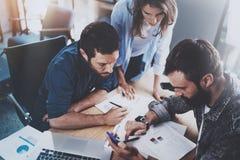 Teamworkarbeteprocess Grupp av unga coworkers som tillsammans arbetar i modern kontorsvind använda för telefon för man mobilt _ Arkivbild