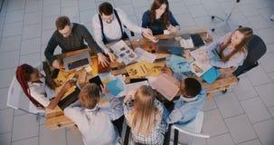 Teamworkbegreppet för den bästa sikten, gruppen av idérikt multietniskt affärsfolk arbetar som ett lag på det moderna sunda  arkivfilmer