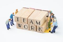 Teamworkbegreppsidé, miniatyrfolkstatyettarbete som laget honom royaltyfri foto