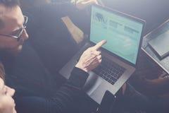 Teamworkprocessbegrepp Två unga kollegor som använder datoren Kvinna som bär den svarta sweatern och sitter på soffan grafer Royaltyfri Bild