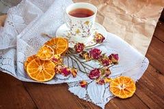 Teapelsiner och blommor på en trätabell Royaltyfri Bild