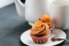 Teapot, ένα φλυτζάνι του τσαγιού και μια καραμέλα cupcake Στοκ Φωτογραφία