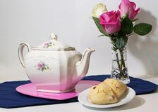 Teapot, βάζο με τα τριαντάφυλλα και ένα πιάτο των scones στοκ φωτογραφία με δικαίωμα ελεύθερης χρήσης