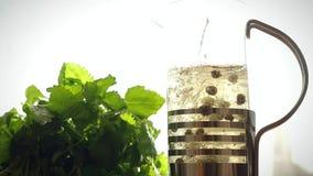 Teapot γυαλιού με το ανθίζοντας λουλούδι τσαγιού μέσα χύστε απόθεμα βίντεο