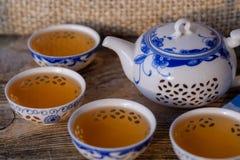 Teapot και κύπελλα πορσελάνης με το πράσινο τσάι στοκ εικόνα