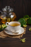 Teapot και το φλυτζάνι με το τσάι και τα λουλούδια στο σκοτεινό ξύλινο πίνακα Στοκ Φωτογραφίες