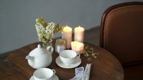 Teapot και φλυτζάνια σε έναν πίνακα φιλμ μικρού μήκους
