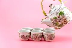 Teapot με τα φλυτζάνια σε ένα ρόδινο υπόβαθρο Στοκ Εικόνες