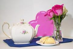 Teapot, ρόδινη καρδιά, τριαντάφυλλα και scones στο πιάτο στοκ φωτογραφίες με δικαίωμα ελεύθερης χρήσης