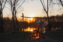 Teapot στην πυρκαγιά προετοιμάζει το τσάι Πορτοκαλί ηλιοβασίλεμα στοκ εικόνα με δικαίωμα ελεύθερης χρήσης