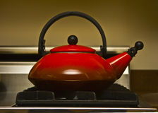 Teapot. Red teapot sitting on a stove Royalty Free Stock Photography