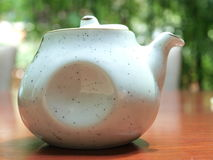 Teapot. A close shot of a Chinese white teapot with the  bamboo in the background Stock Photo