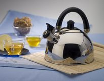 Teapot. Brilliant teapot on a table, cups and cookies Stock Image