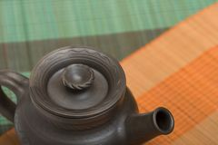 Teapot. Clay teapot on the red and green background stock photos