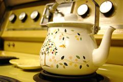 Teapot. This teapot is hand painted and looks great sitting on this retro yellow oven Stock Photo