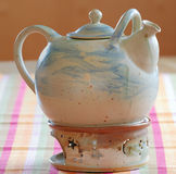Teapot. A clay teapot with its warmer standing on the table royalty free stock image