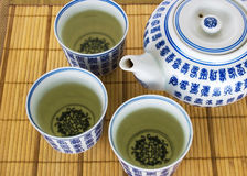 Teapot 4. Teapot and three cups with green tea Stock Image