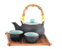 Teapot. Oriental style teapot and two tea cups on a wooden tray Royalty Free Stock Images